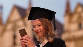 Young cute student graduate texting message on her phone.