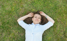 Young cute student having fun on the grass in the park Royalty Free Stock Photos