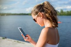 Young cute teen girl reading sms on her smartphone, view from be royalty free stock photography