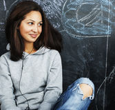 Young cute teenage girl in classroom at blackboard seating on ta Royalty Free Stock Photos
