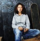 Young cute teenage girl in classroom at blackboard seating on ta Royalty Free Stock Photo