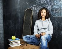 Young cute teenage girl in classroom at blackboard seating on ta Stock Photography
