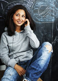 Young cute teenage girl in classroom at blackboard seating on ta Stock Photo