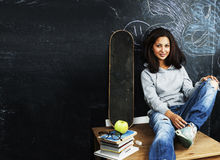 Young cute teenage girl in classroom at blackboard seating on ta Royalty Free Stock Image