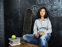 Young cute teenage girl in classroom at blackboard seating on ta Stock Image