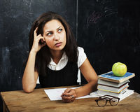 Young cute teenage girl in classroom at blackboard seating on ta Stock Photo