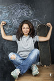 Young cute teenage girl in classroom at blackboard seating on table smiling Stock Image