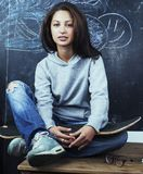 Young cute teenage girl in classroom at blackboard seating on ta Stock Images
