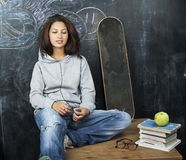 Young cute teenage girl in classroom at blackboard seating on table smiling, modern pupil hipster concept, lifestyle Royalty Free Stock Photography