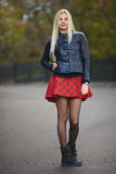 Young cute trendy dressed blonde woman strolling autumnal park posing outdoors against blurry foliage background Royalty Free Stock Photos
