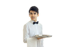 Young cute waiter looks forward to smiling and holding a towel with a tray Royalty Free Stock Images