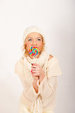 Young cute winter girl with lollipop candy. Young cute winter girl in white knit clothes with big colored lollipop candy. gray background Stock Image