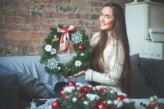 Young Cute Woman with Christmas Evergreen Tree Wreath royalty free stock image
