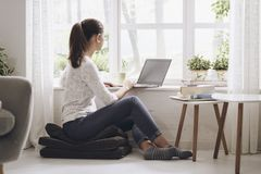 Young woman networking with her laptop at home stock images