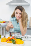Young cute woman cooking while smiling at camera Royalty Free Stock Photography