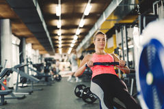 Young cute woman doing exercises with rowing machine. In gym royalty free stock images