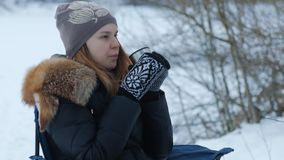 Young cute woman drinking hot tea from a thermos outside in winter time. stock footage