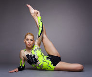 Young cute woman in gymnast suit doing split Stock Photography