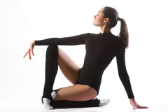 Young cute woman in gymnast suit show athletic skill on white background Royalty Free Stock Photography
