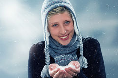 Young cute woman with a hand full of snow Royalty Free Stock Images