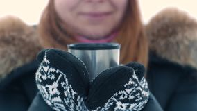 Young cute woman holding a cup with hot tea from a thermos outside in winter time. stock footage