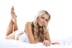 A young and cute woman laying on white silk Stock Photos