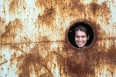Young cute woman looks from the window of a rusty industrial objects. Royalty Free Stock Photos