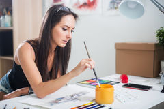 Young cute woman painting aquarelle picture portrait of a artist at the workplace Stock Image