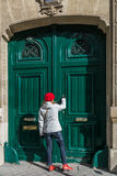 Young cute woman with red hat and shoes, knocking at a vintage green wooden door. Royalty Free Stock Image