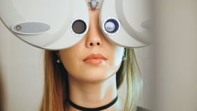 Young cute woman with red lips checks the eyes on the modern equipment in the medical center Stock Photo