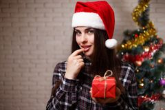 Young cute woman in Santa cap got a present on christmas tree ba. Ckground.Portrait of a beautiful woman with a gift box. New Year, Christmas, gift, surprise Royalty Free Stock Photos