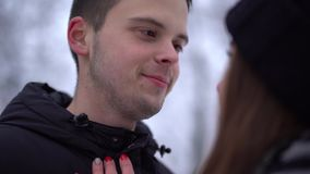 Young cute woman and tall man looking into each other`s eyes in winter clothing. Woman caress face of boyfriend. Happy. Young woman and tall man looking into stock video footage