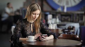 Young cute woman using phone ,sitting at a cafe holding a smartphone, answering texts. Beautiful business woman in a stock video