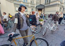 Young cute woman in vintage clothing ready for cycling on old bicycle at fashion festival Retro Cruise Royalty Free Stock Image