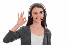 Young cutie brunette business woman with headphones and microphone smiling and and showing OK isolated on white Royalty Free Stock Photos