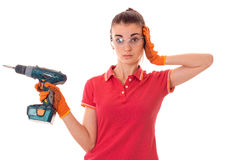 Young cutie woman with dark hair in uniforl makes renovations with drill in her hands isolated on white background Stock Photography
