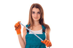 Young cutie woman with dark hair in uniforl makes renovations with measure tape in her hands isolated on white Royalty Free Stock Photo