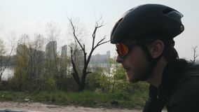 Young cyclist with beard wearing sunglasses, helmet and black outfit riding a bicycle. Close up side view. Cycling concept. Slow m stock video footage