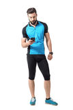 Young cyclist in blue jersey t-shirt looking at smartphone cycling app. Royalty Free Stock Images