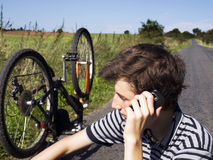 Young cyclist calling for help Royalty Free Stock Image