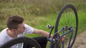Young cyclist checking his bike outdoor stock footage