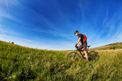 Young cyclist cycling on the green meadow against beautiful blue sky with clouds in the countryside. Royalty Free Stock Images