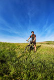 Young cyclist cycling on the green meadow against beautiful blue sky with clouds in the countryside. Stock Photos