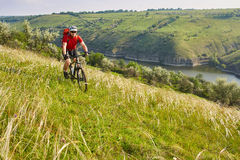 Young cyclist cycling in the green summer meadow against beautiful landscape. Attractive sportsman in the sportwear, with helmet, backpack and sunglasses Royalty Free Stock Photography