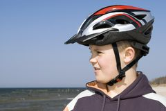 Young cyclist in helmet. A young cyclist boy wearing a protective bike helmet. Standing on a beach, looking at the sea Stock Photos