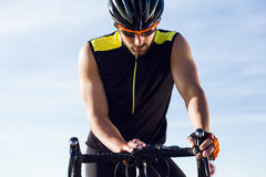 Young cyclist man setting timer on bicycle in sports gear. Stock Photos