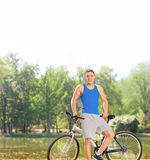 Young cyclist posing with his bicycle by a pond Stock Photo