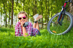 Young cyclist relaxation lying in the grass Stock Photography