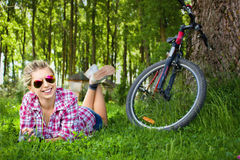 Young cyclist relaxation lying in the grass Royalty Free Stock Photography
