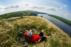 Young cyclist resting on the meadow on reverside in mountains with mountain bicycle against beautiful sky. Stock Photos